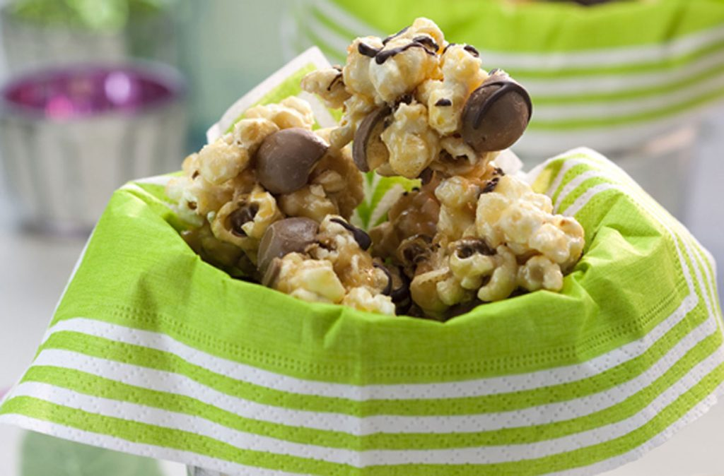Malteser and popcorn bites piled up in a bowl with a napkin