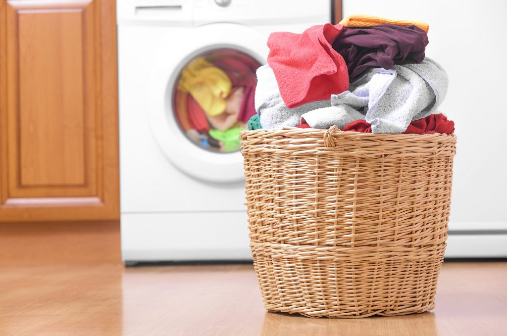 Basket of laundry in front of a washing machine